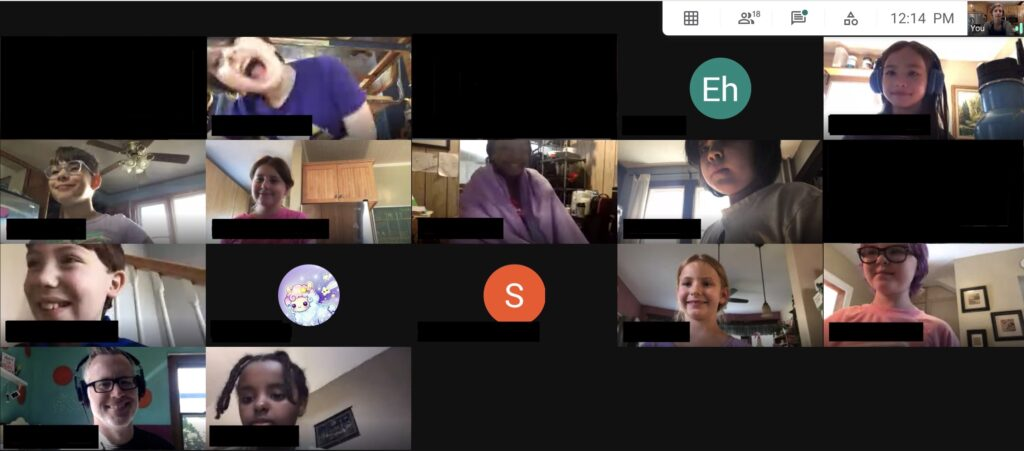 A screen capture of a virtual classroom, showing a grid of students who have joined a virtual meeting due to the COVID-19 pandemic. Several students have their cameras in and are showing their smiling faces. Some students have their cameras off and display initials or avatars. The teacher smiles and wears headphones.